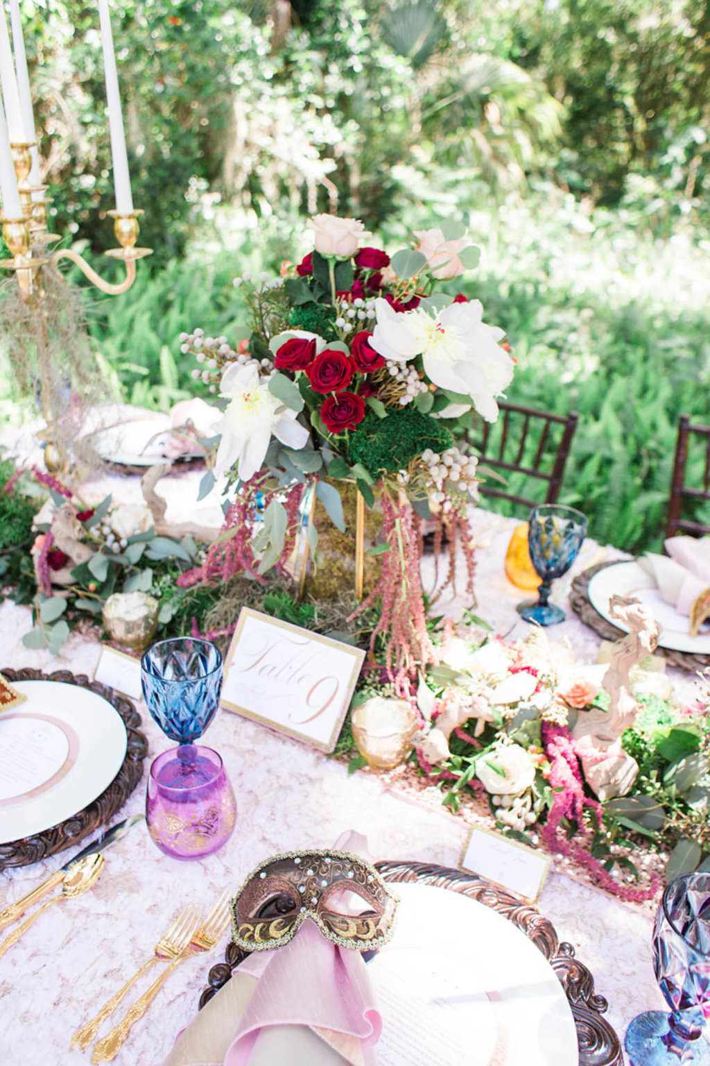 Outdoor Whimsical Boho Garden Wedding Reception Decor with Vintage Mismatched Dishes and Garland Floral Table Runner and Red and White Centerpiece