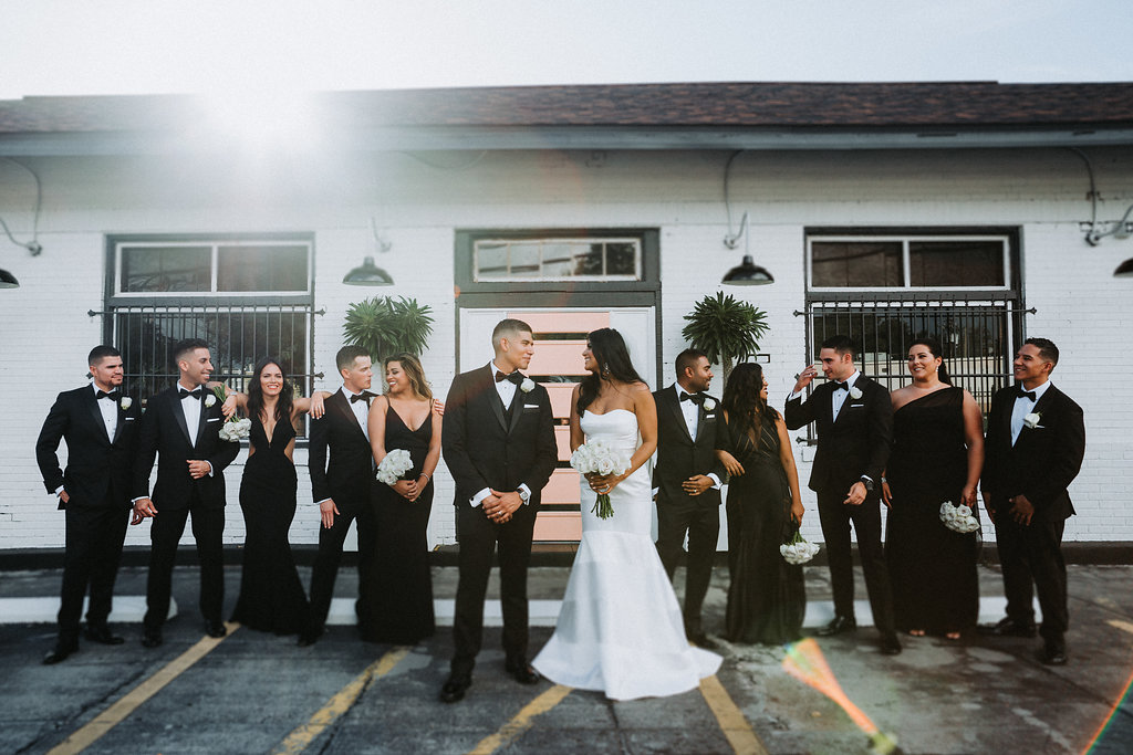 Outdoor Industrial Modern Indian Wedding Party Portrait, Bridesmaids in Mismatched Black Floor Length Dresses, Groom in Black Tuxedo with White Boutonniere, Bride in Strapless Mermaid Wedding Dress with White Bouquet   Tampa Bay Wedding Photographer Grind and Press Photography