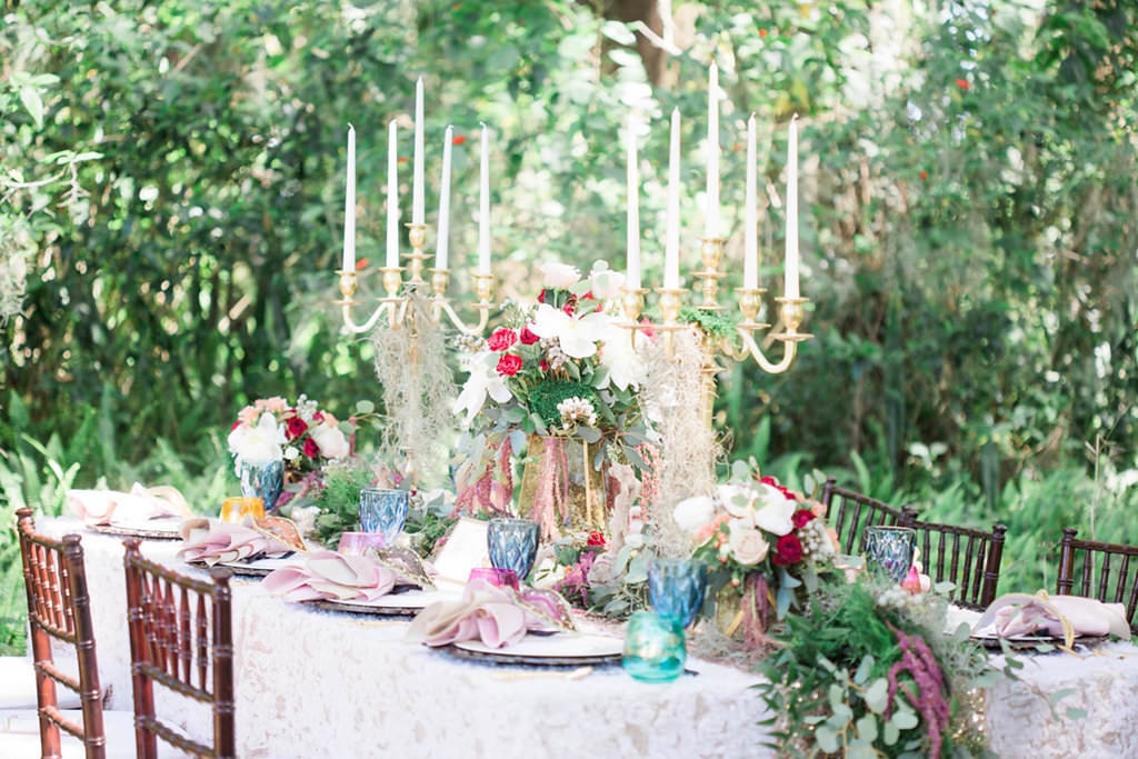 Outdoor Whimsical Boho Garden Wedding Reception Decor with Vintage Mismatched Dishes and Garland Floral Table Runner and Candelabra Centerpiece   Over the Top Rental Linens