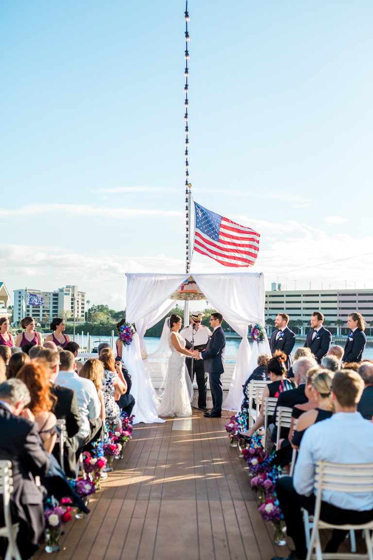 Outdoor On the Water Wedding Ceremony Portrait with White Folding Chairs, White Draped Chuppah Wedding Arch with Purple, Blue, White, and Red Flower Arrangements | Tampa Bay Nautical Wedding Venue Yacht StarShip