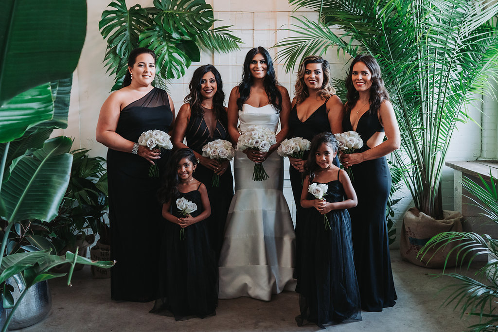 Modern Indian Wedding Bridal Party Portrait, Bridesmaids and Flower Girls in Mismatched Floor Length Black Dresses, Bride in Strapless Mermaid Wedding Dress, with White Rose Bouquet   Tampa Wedding Photographer Grind and Press Photography