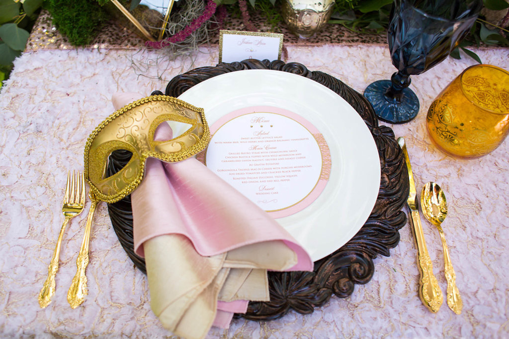 Outdoor Whimsical Boho Garden Wedding Reception Decor with Gold Venetian Mask, Wood Charger, Gold Flatware and Pink Textured Linen   Over the Top Rental Linens