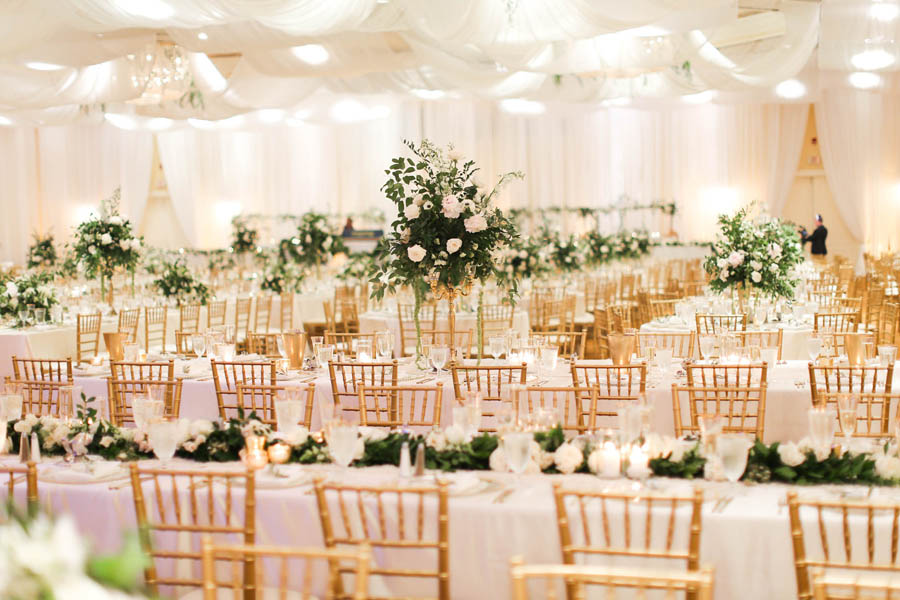 White and Greenery Ballroom Wedding Reception with Long Feasting Tables, Tall White Floral and Greenery Centerpiece in Gold Candelabra, and Long Garland Centerpiece, with Gold Chiavari Chairs   White Ceiling Draping by Tampa Bay Gabro Event Services   Tarpon Springs Wedding Venue Inverness Hall at Innisbrook Resort