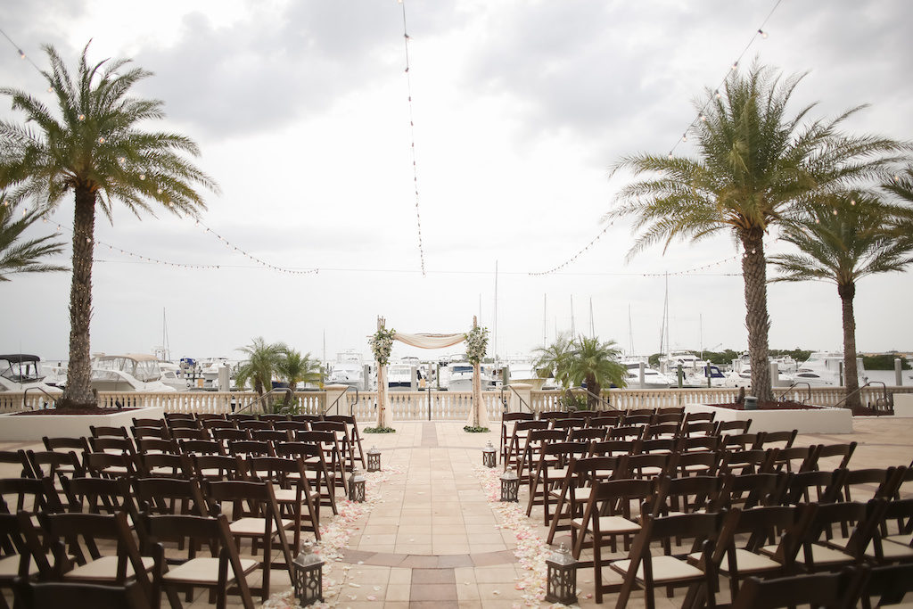 Rustic Nautical Outdoor Waterfront Marina Wedding Ceremony Decor with Brown Wood Folding Chairs, Rustic Hurricane Lanterns, Blush Pink Rose Petal Aisle, String Lights, and White Draped with Floral and Greenery Arch | Tampa Bay Wedding Venue The Westshore Yacht Club