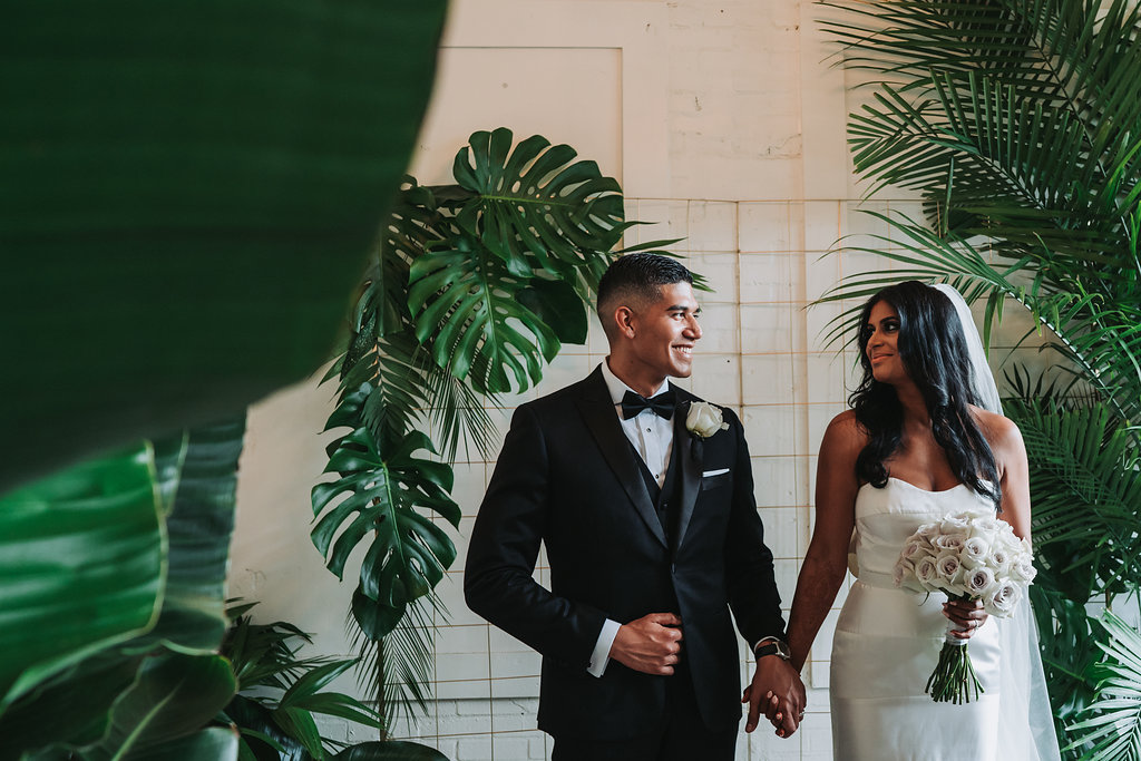 Modern Indian Wedding Bride and Groom Portrait, Bride in Strapless Wedding Dress, Groom in Black Tuxedo with White Rose Boutonniere and White Rose Bouquet   Tampa Wedding Photographer Grind and Press Photography