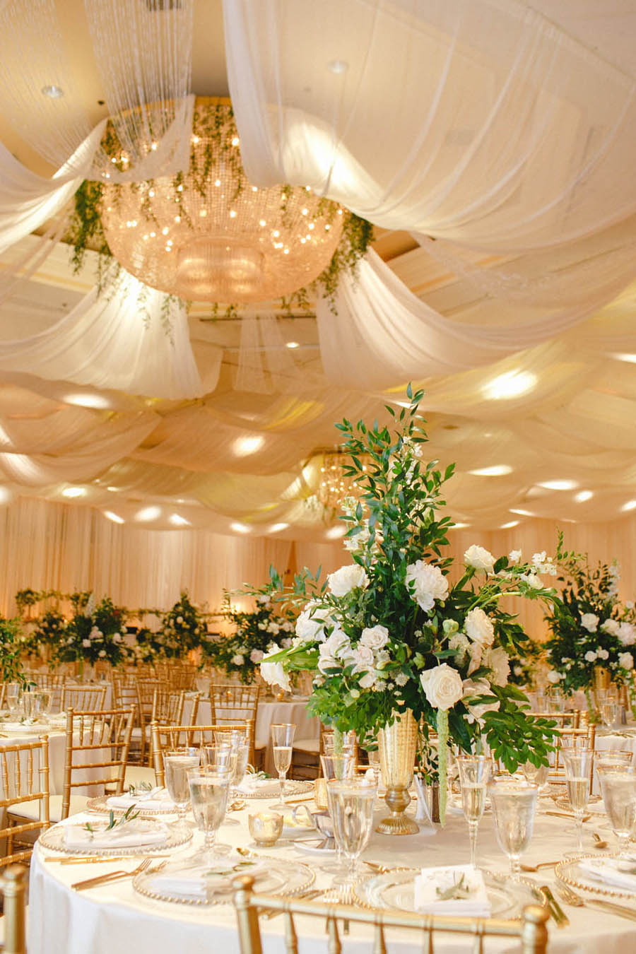 White and Greenery Ballroom Wedding Reception with Tall White Floral and Greenery Centerpiece in Gold Vase with Gold Chiavari Chairs | White Ceiling Draping by Tampa Bay Gabro Event Services | Tarpon Springs Wedding Venue Inverness Hall at Innisbrook Resort