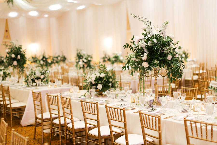 White and Greenery Ballroom Wedding Reception with Long Feasting Tables, Tall White Floral and Greenery Centerpiece in Gold Candelabra, with Gold Chiavari Chairs   White Ceiling Draping by Tampa Bay Gabro Event Services   Tarpon Springs Wedding Venue Inverness Hall at Innisbrook Resort