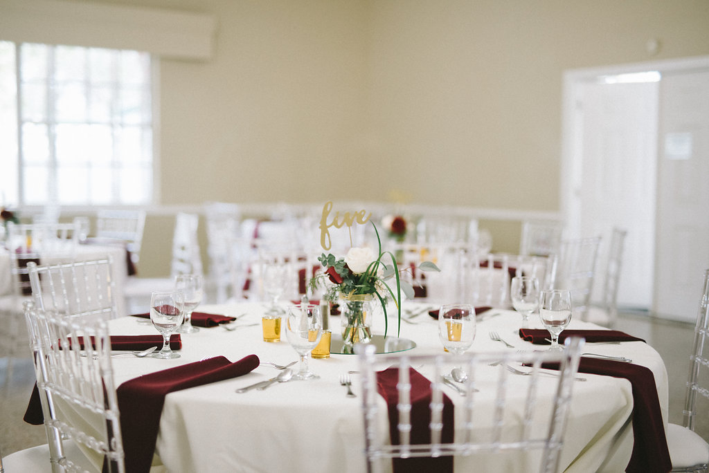 Gold And Burgundy Wedding Reception Table Decor With Clear Plastic Chiavari Chairs Red Napkins White Linen Gold Table Number And Votive Candle Holders And Small White And Red Rose With Greenery Bouquet