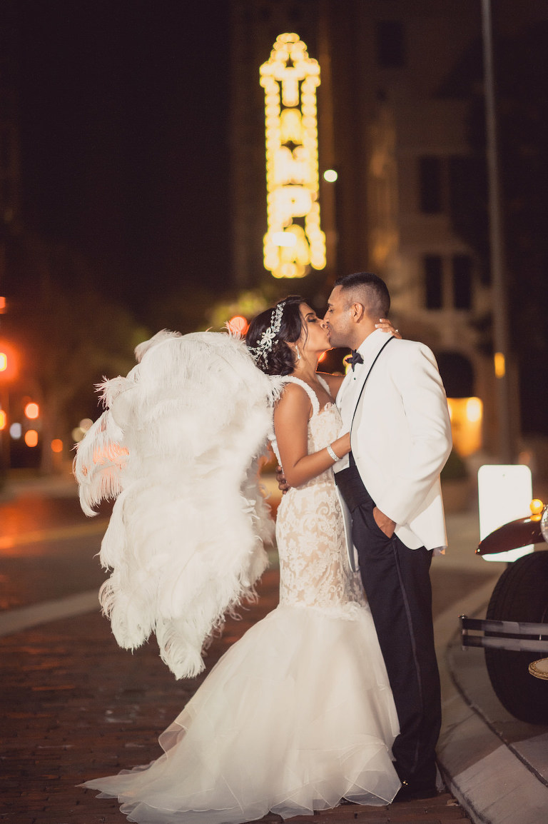 Outdoor Nighttime Downtown Tampa Bride and Groom Portrait, Bride in Lace Layered Mermaid Ines Di Santo Dress, Groom in White Tuxedo with Hora Loca Props Angel Wings | Tampa Bay Wedding Planner Special Moments Event Planning | Dress Shop Isabel O'Neil Bridal