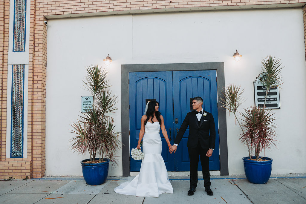 Outdoor Downtown Tampa Modern Indian Wedding Bride and Groom Portrait, Bride in Strapless Mermaid Wedding Dress, Groom in Black Tuxedo with White Rose Boutonniere   Wedding Photographer Grind and Press Photography