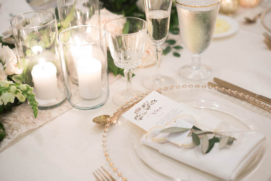 White and Greenery Wedding Reception Table Setting with Gold Beaded Glass Charger, White Linens, Pillar Candles in Glass Cylinders   Tampa Bay Flatware and Glass Rentals A Chair Affair