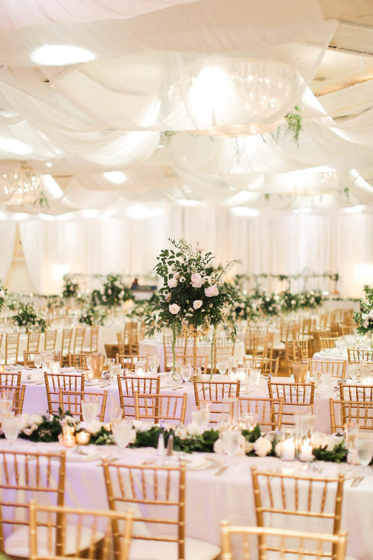 White and Greenery Ballroom Wedding Reception with Long Feasting Tables, Tall White Floral and Greenery Centerpiece in Gold Candelabra, and Long Garland Centerpiece, with Gold Chiavari Chairs | White Ceiling Draping by Tampa Bay Gabro Event Services | Tarpon Springs Wedding Venue Inverness Hall at Innisbrook Resort