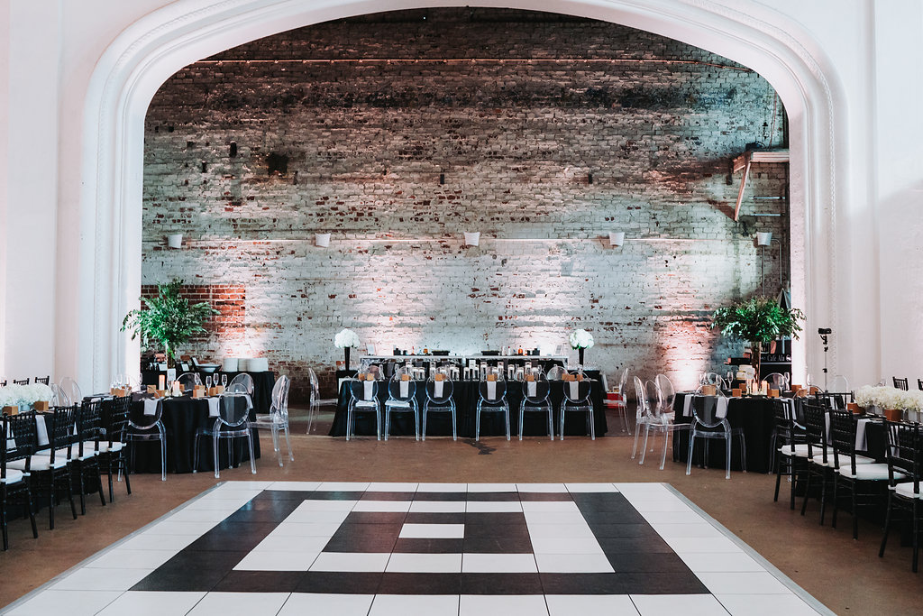 Modern Black and White Indian Wedding Reception with Black Linens, Clear Plastic Oval Back and Black Chiavari Chairs, and Tall Greenery Centerpieces and Black and White Geometric Dancefloor   Tampa Bay Historic Wedding Venue The Rialto Theater   Planner Glitz Events