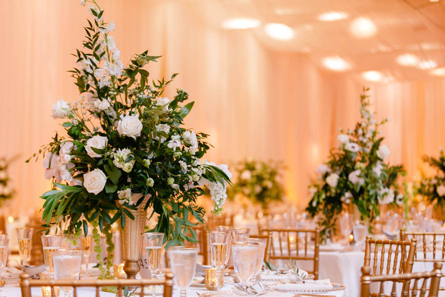White and Greenery Ballroom Wedding Reception Tall Centerpiece in Gold Candelabra, Small Votive Candles, and Gold Chiavari Chairs