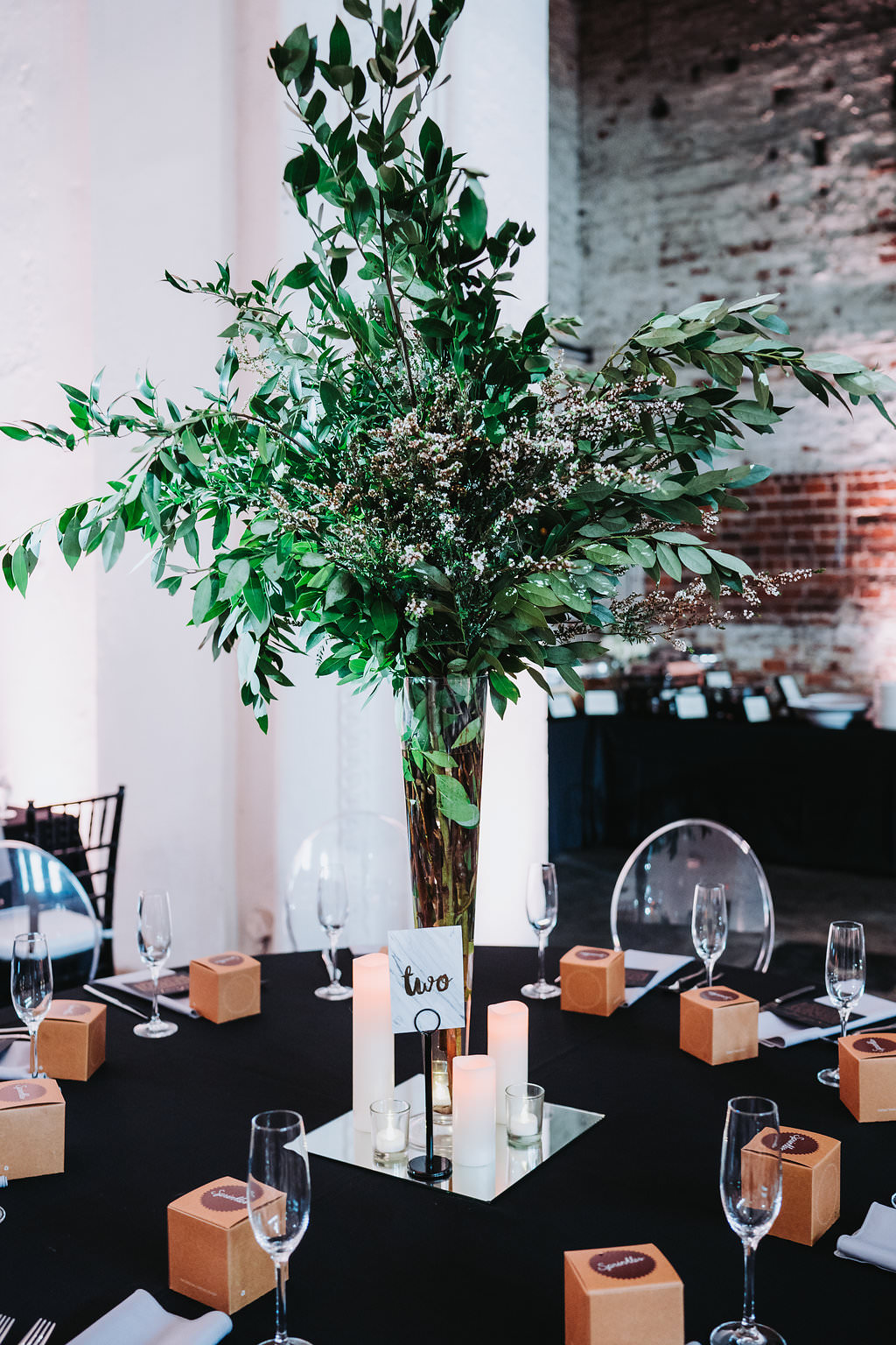 Modern Black and White Indian Wedding Reception with Black Linens, and Tall Greenery Centerpieces in Clear Vases with Pillar Candles   Tampa Bay Historic Wedding Venue The Rialto Theater   Planner Glitz Events