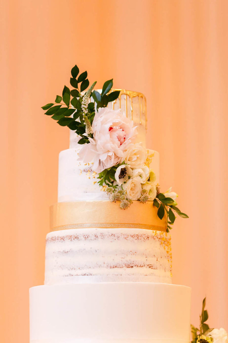 Nine Tier Round White Wedding Cake with Gold Dripping Frosting, White Florals with Greenery | Tarpon Springs Wedding Bakery Artistic Whisk