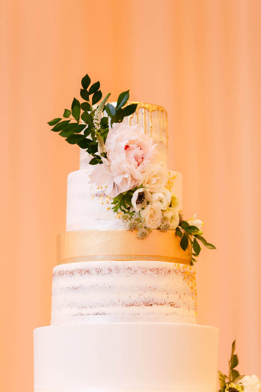 Nine Tier Round White Wedding Cake with Gold Dripping Frosting, White Florals with Greenery   Tarpon Springs Wedding Bakery Artistic Whisk