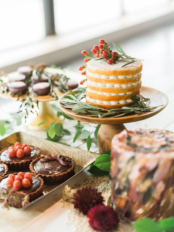 Modern Wedding Dessert Bar with Five Layer Round Bare Layer Cake, Chocolate Tarts, and Macaroons