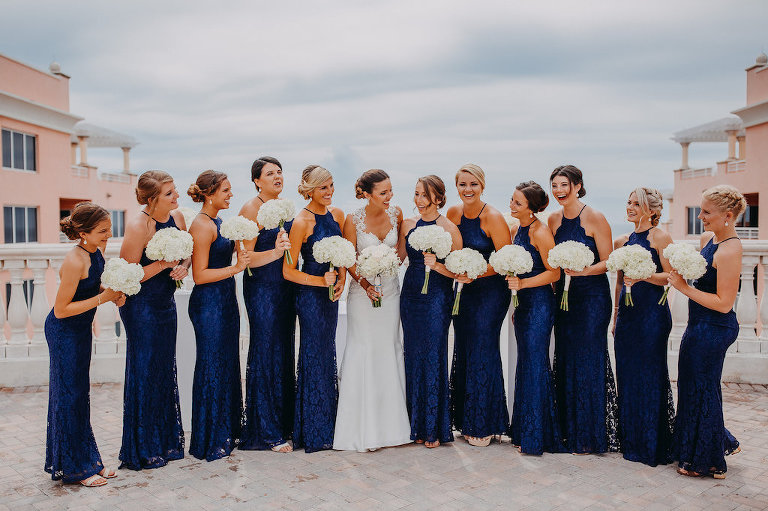 Outdoor Rooftop Bridal Party Portrait, Bridesmaids in Halter Navy Blue Column Lulu's Zenith Dresses, Bride in Lace Cap Sleeve A Line Sincerity Bridal Wedding Dress, with White Floral Bouquet | Tampa Bay Wedding Photography Rad Red Creative | Waterfront Hotel Wedding Venue Hotel Venue Hyatt Regency Clearwater Beach