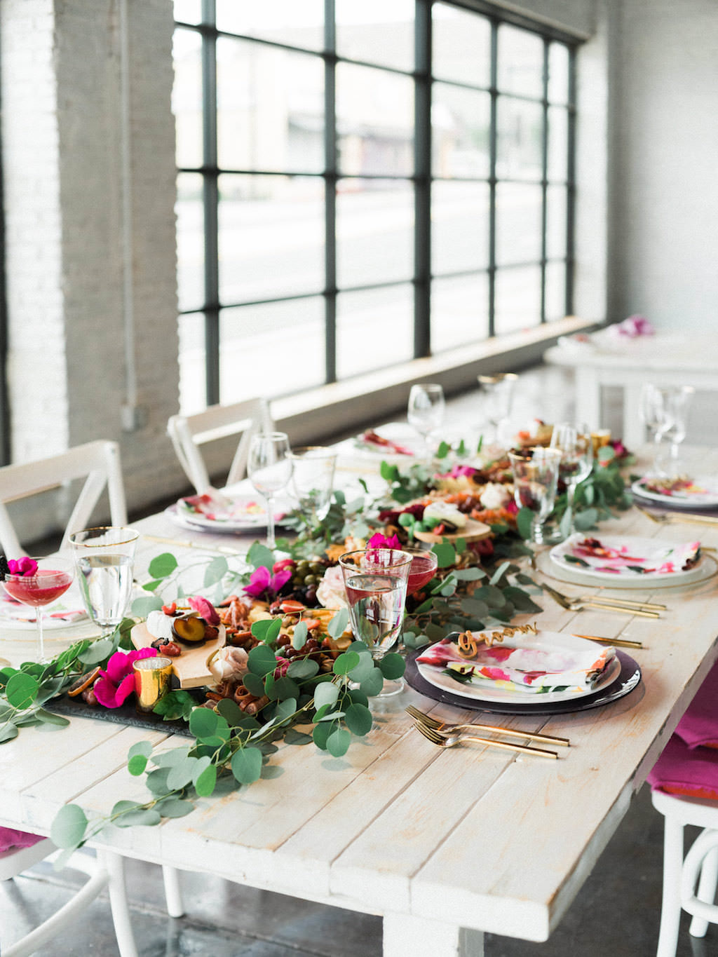 Modern Fuchsia Wedding Reception Table with Charcuterie Board with Greenery, Wooden Table, White Cross Back Chairs, Pink Linens   Lakeland Florida Wedding Caterer Tastes of Tampa Bay   Furniture and Dish Rentals A Chair Affair   Venue Haus 820