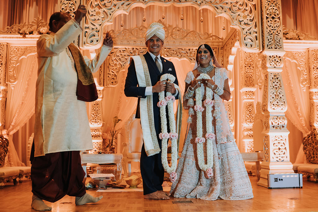 Regal and Romantic Traditional Hindu Indian Wedding Reception Bride and Groom Portrait with Gold Uplighting and Blush Pink Draping Behind the Mandap   Tampa Bay Wedding Venue Safety Harbor Resort and Spa   Planner Glitz Events   Photographer Grind and Press Photography