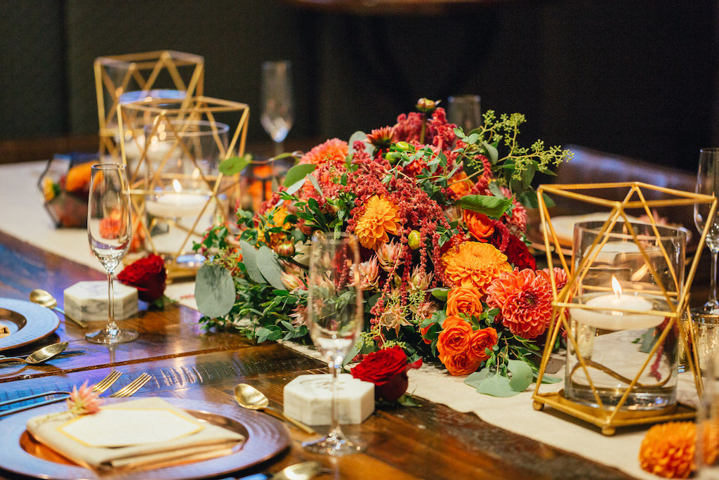 Intimate Wedding Reception Table Decor with Floating Votive Candles in Brass Geometric Holders with Red and Orange Floral Centerpiece with Greenery on Simple Linen Runner with Marble Place Cards and Gold Flatware | Tampa Wedding Planner UNIQUE Weddings and Events | Rentals Over The Top Linens