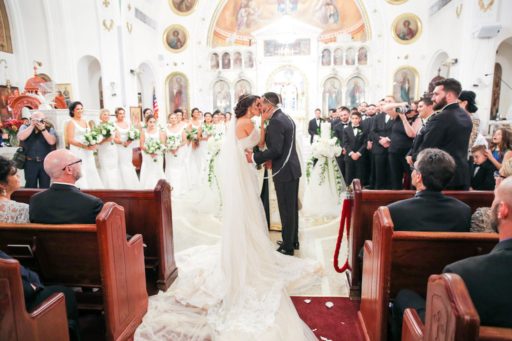 Greek Wedding Ceremony Kiss Portrait with Bridesmaids in Floorlength White Dresses, Groomsmen in Black Tuxes with White Boutonniere   Tarpon Springs Traditional Wedding Venue St. Nicholas Greek Orthodox