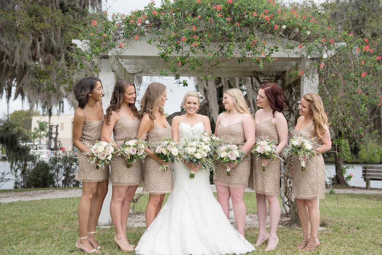 Outdoor Garden Bridal Party Portrait, Bride in Strapless Mermaid Allure Bridals Dress, Bridesmaids in Beige Spaghetti Strap Sequined Beaded Short Adrianna Papell Dresses with White and Ivory Floral with Natural Greenery Bouquets | Sarasota Historic Waterfront Wedding Venue The Edson Keith Mansion | Photographer Kristen Marie Photography