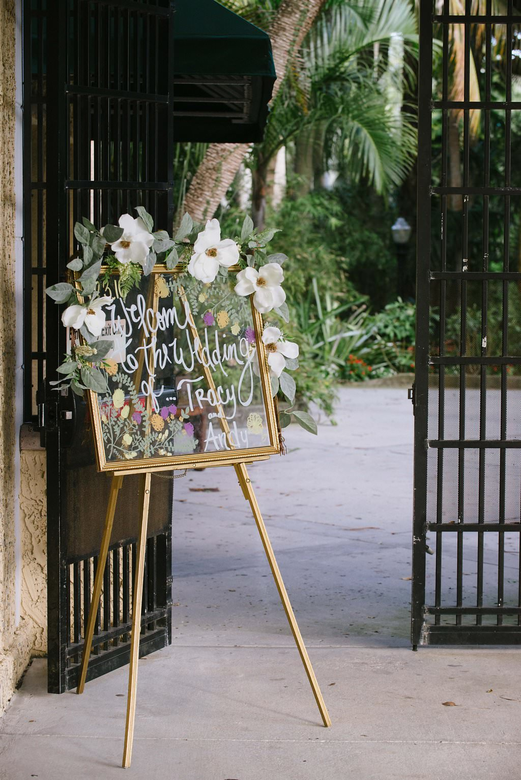 Outdoor Garden Wedding Welcome Sign, Handwritten on Glass in Gold Frame with Large White Flowers and Greenery