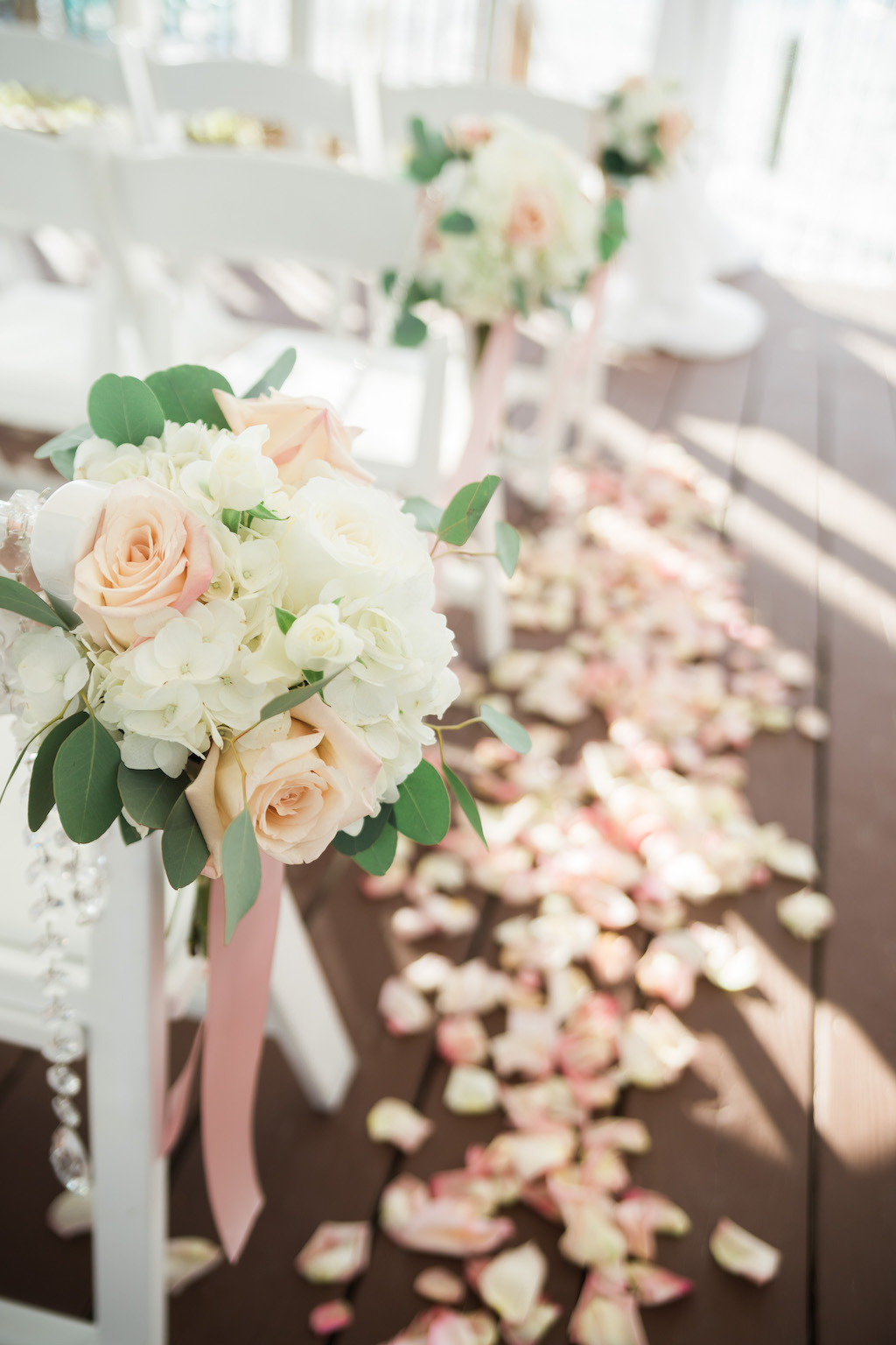 Outdoor Whimsical Beach Deck Wedding Ceremony Decor with White Folding Chairs with Blush Rose and White Hydrangea with Greenery and Long Pink Ribbon and Jewels, Pink Rose Petal Aisle