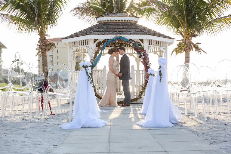 Outdoor Beach Wedding Ceremony at Gazebo with Clear Plastic Chairs, White Draping, Whimsical Purple, Black, Magenta, Fuchsia, Plum and White Floral Wedding Arch with Greenery with Turquoise Draping | Tampa Bay Wedding Florist Gabro Event Services | Waterfront Venue Isla Del Sol Yacht and Country Club | Planner Kelly Kennedy Weddings and Events | Photographer Lifelong Studios Photography