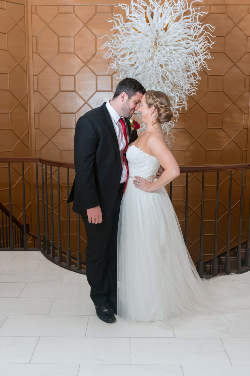Indoor Wedding Portrait with Glass Chandelier, Bride in Strapless A Line Maggie Sottero Dress, Groom with Red Tie and Red Rose Boutonniere | Tampa Bay Wedding Photographer Carrie Wildes Photography | Downtown Wedding Venue The Tampa Club