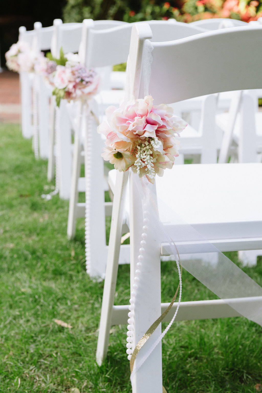 Outdoor Garden Wedding Ceremony Decor with White Folding Chairs with Pink and White Flowers, Pearl Beads, and Gold Ribbon