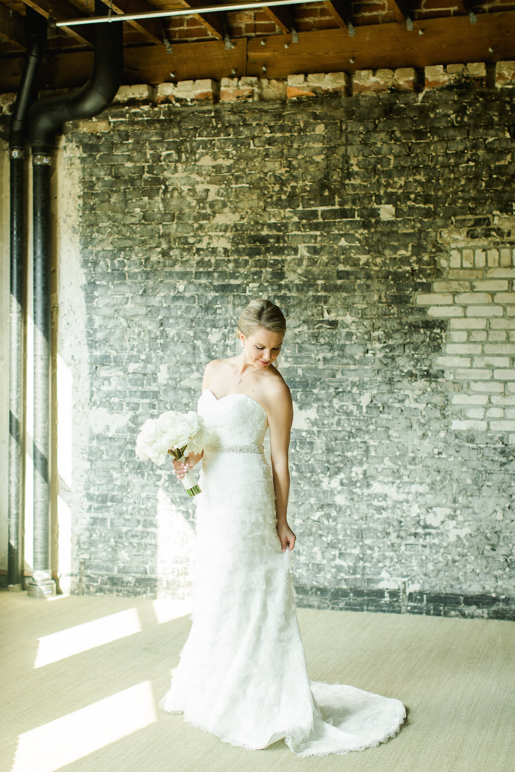 Industrial Indoor Bridal Portrait in Strapless Belted Robert Bullock Wedding Dress with White Floral Bouquet   Tampa Bay Wedding Photographer Ailyn La Torre Photography   Venue The Oxford Exchange