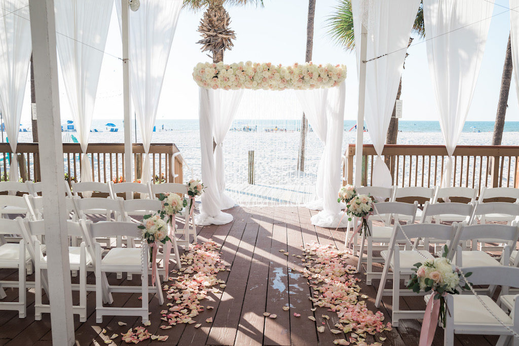 Outdoor Beachfront Sandpiper Deck Wedding Ceremony with White Folding Chairs, Blush Pink Rose Petal Aisle, White Floral with Greenery and Pink Ribbon, and White Draped Chuppah Wedding Arch with White and Pink Floral | Tampa Bay Event Draping and Rentals Gabro Event Services | Clearwater Beach Wedding Venue Hilton Clearwater Beach