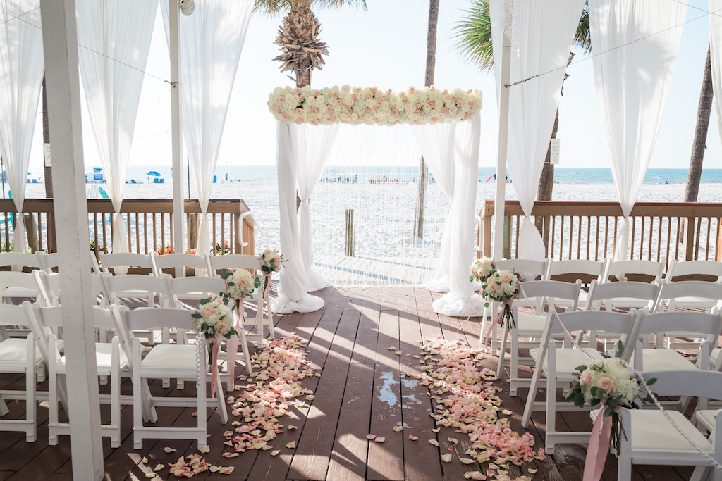 Outdoor Beachfront Sandpiper Deck Wedding Ceremony with White Folding Chairs, Blush Pink Rose Petal Aisle, White Floral with Greenery and Pink Ribbon, and White Draped Chuppah Wedding Arch with White and Pink Floral   Tampa Bay Event Draping and Rentals Gabro Event Services   Clearwater Beach Wedding Venue Hilton Clearwater Beach