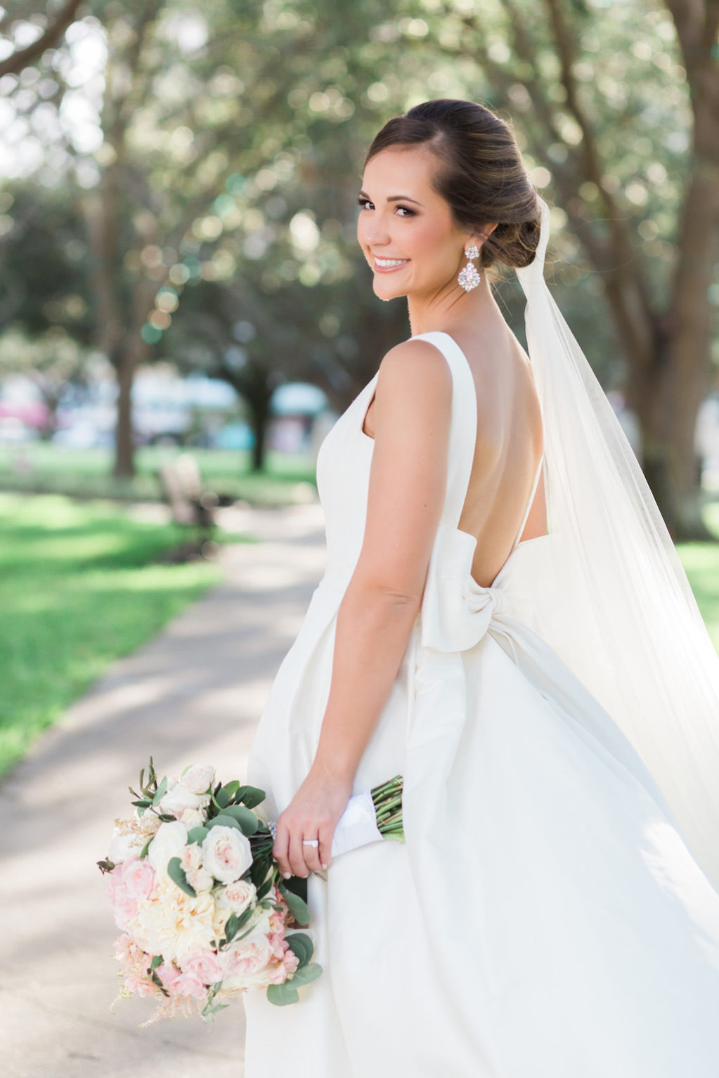 Outdoor Park Bridal Wedding Portrait in Open Back with Bow Rosa Clara Bridal Dress, with Blush Pink and White Peony Bouquet with Greenery, Comb Veil and Large Drop Earrings | St Pete Wedding Hair and Makeup Michele Renee The Studio