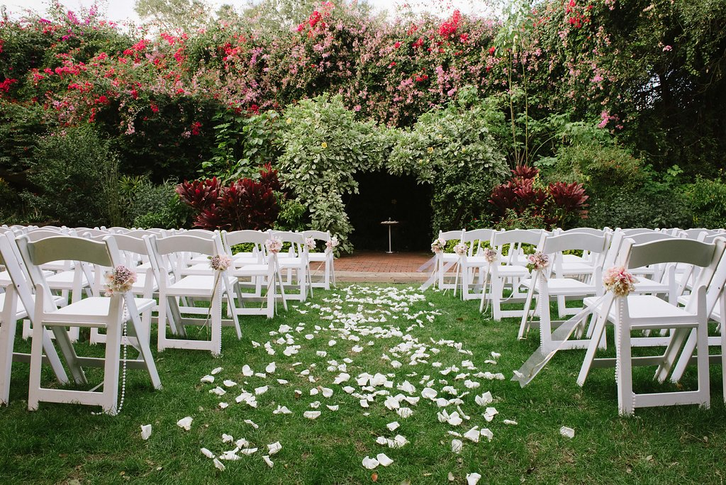Outdoor Garden Wedding Ceremony Decor With White Folding Chairs With Pink And White Flowers Pearl Beads And Gold Ribbon St Pete Wedding Ceremony Venue The Sunken Gardens Marry Me Tampa