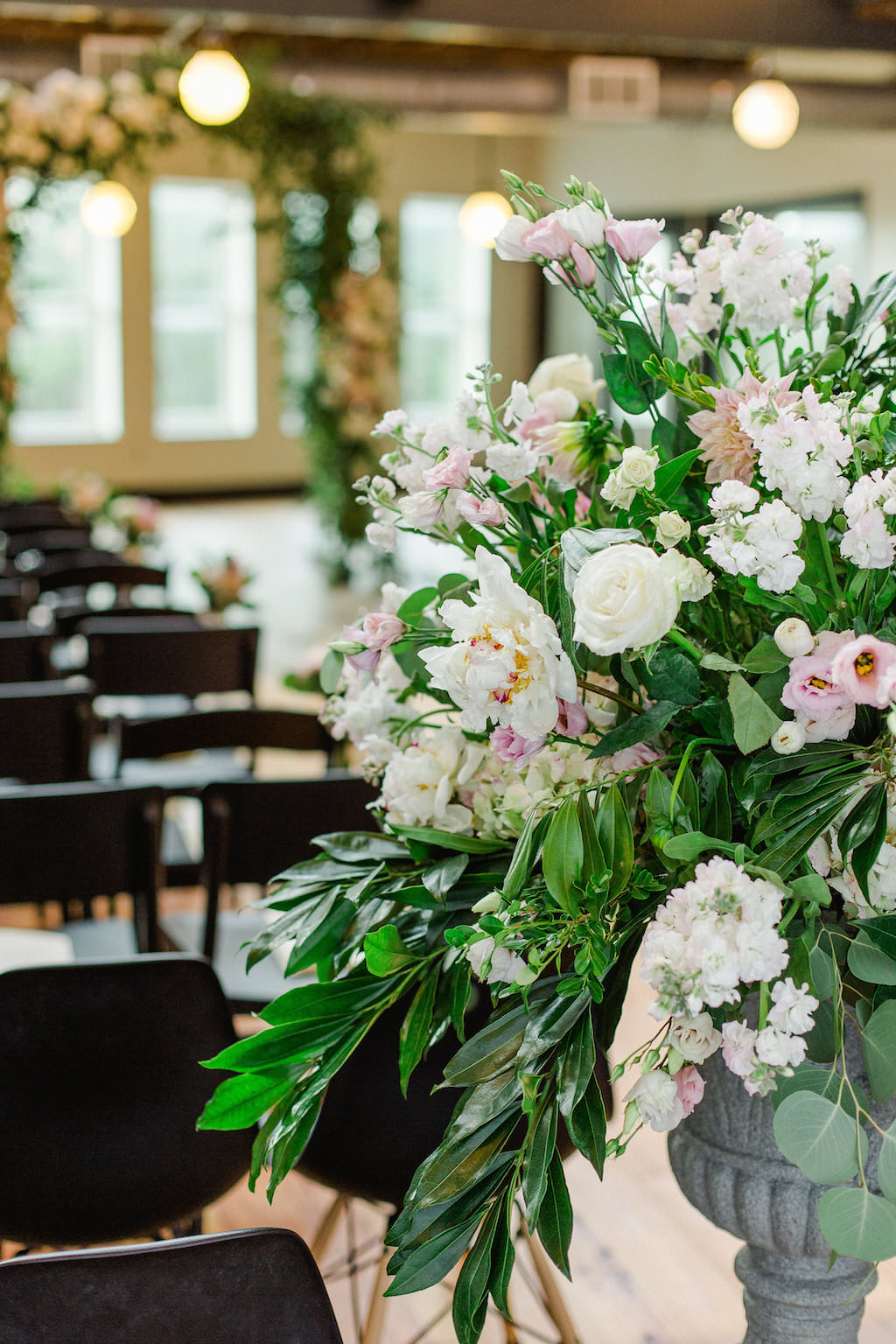 Indoor Industrial Wedding Ceremony Decor with Floral and Greenery Arch, White and BLush Flower with Natural Greenery in Tall Planter, and Mismatched Dark Wooden Chairs