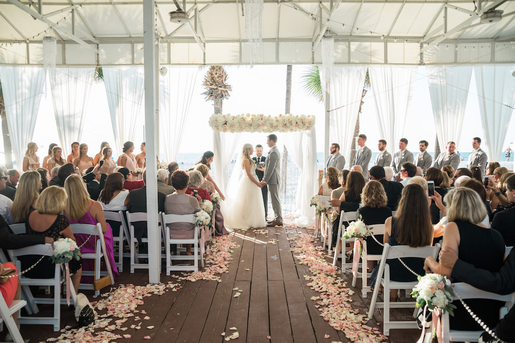Outdoor Beachfront Sandpiper Deck Wedding Ceremony Portrait with White Folding Chairs, Blush Pink Rose Petal Aisle, White Floral with Greenery and Pink Ribbon, and White Draped Chuppah Wedding Arch with White and Pink Floral, Groomsmen in Light Gray Suits, Bridesmaids in Pink   Tampa Bay Event Draping and Rentals Gabro Event Services   Clearwater Beach Wedding Venue Hilton Clearwater Beach