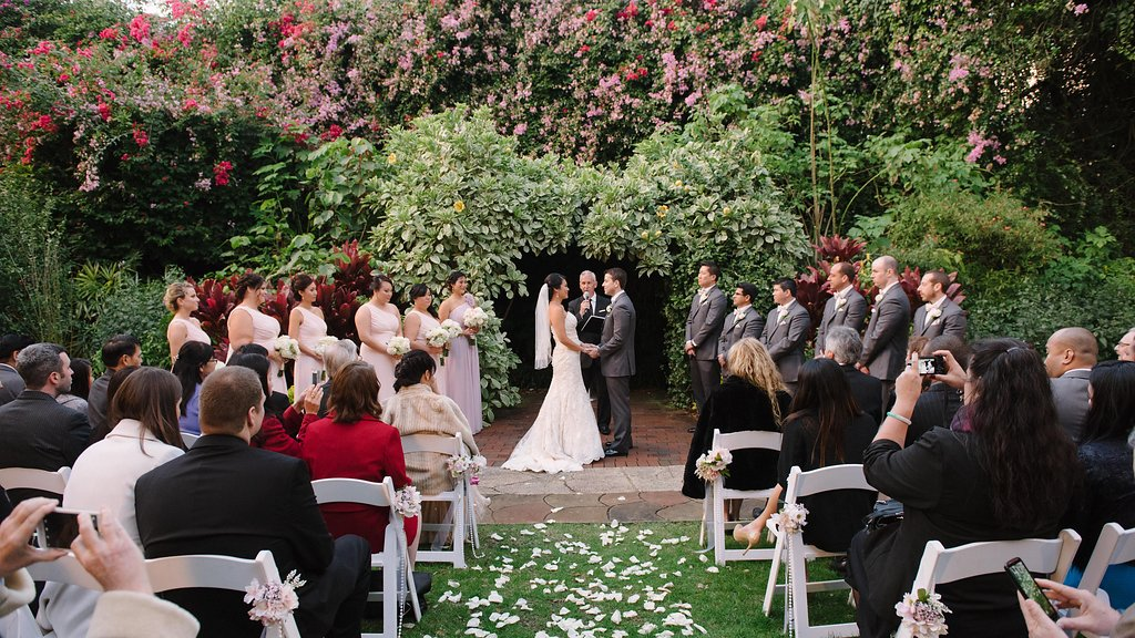 Outdoor Garden Wedding Ceremony Portrait, with White Folding Chairs with Pink and White Flowers, Pearl Beads, and Gold Ribbon, Bridesmaids in Off the Shoulder Blush PInk Dresses, Groomsmen in Gray Suits   St Pete Wedding Ceremony Venue The Sunken Gardens