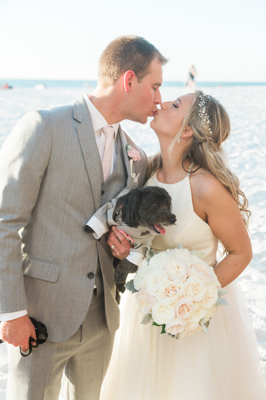 Outdoor Beach Wedding Bride and Groom Portrait With Dog wearing Mini Gray Suit, Groom in Gray Suit with BLush PInk Tie and Rose Boutonniere, Bride in Halter Ballgown Hayley Paige Wedding Dress with White Rose Bouquet and Jeweled Headband   Whimsical Clearwater BeachWedding