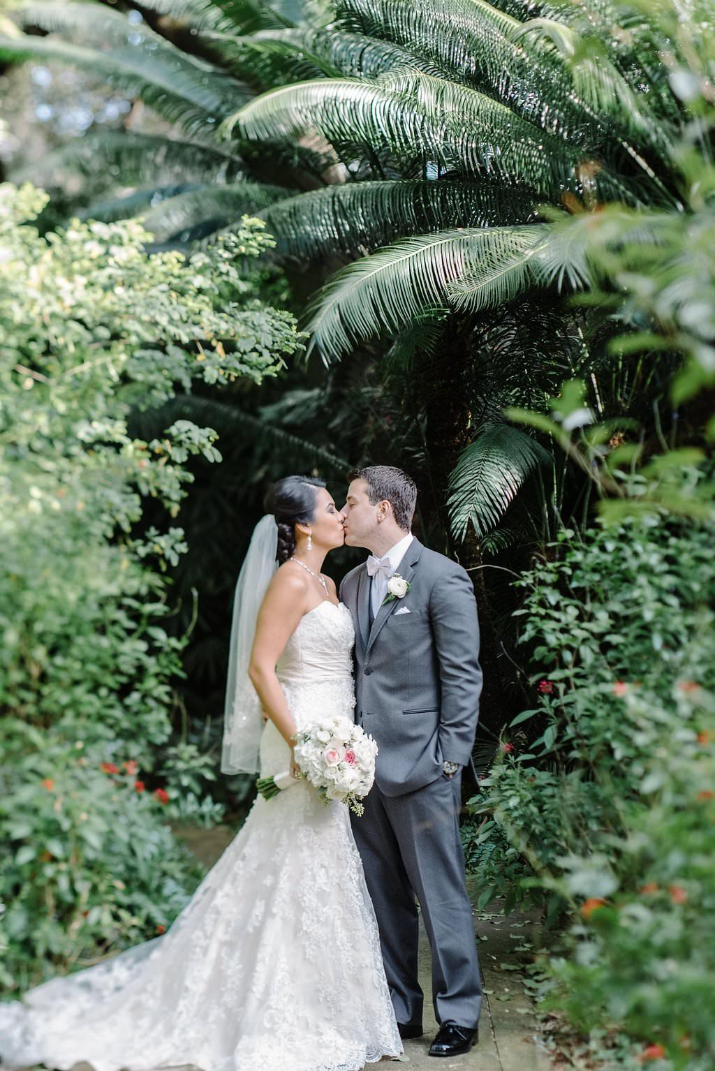 Outdoor Tropical Garden Bride and Groom Wedding Portrait, Bride in Strapless Lace Allure Bridal Dress with Comb Veil, Groom in Grey Suit   St Pete Wedding Venue Sunken Gardens