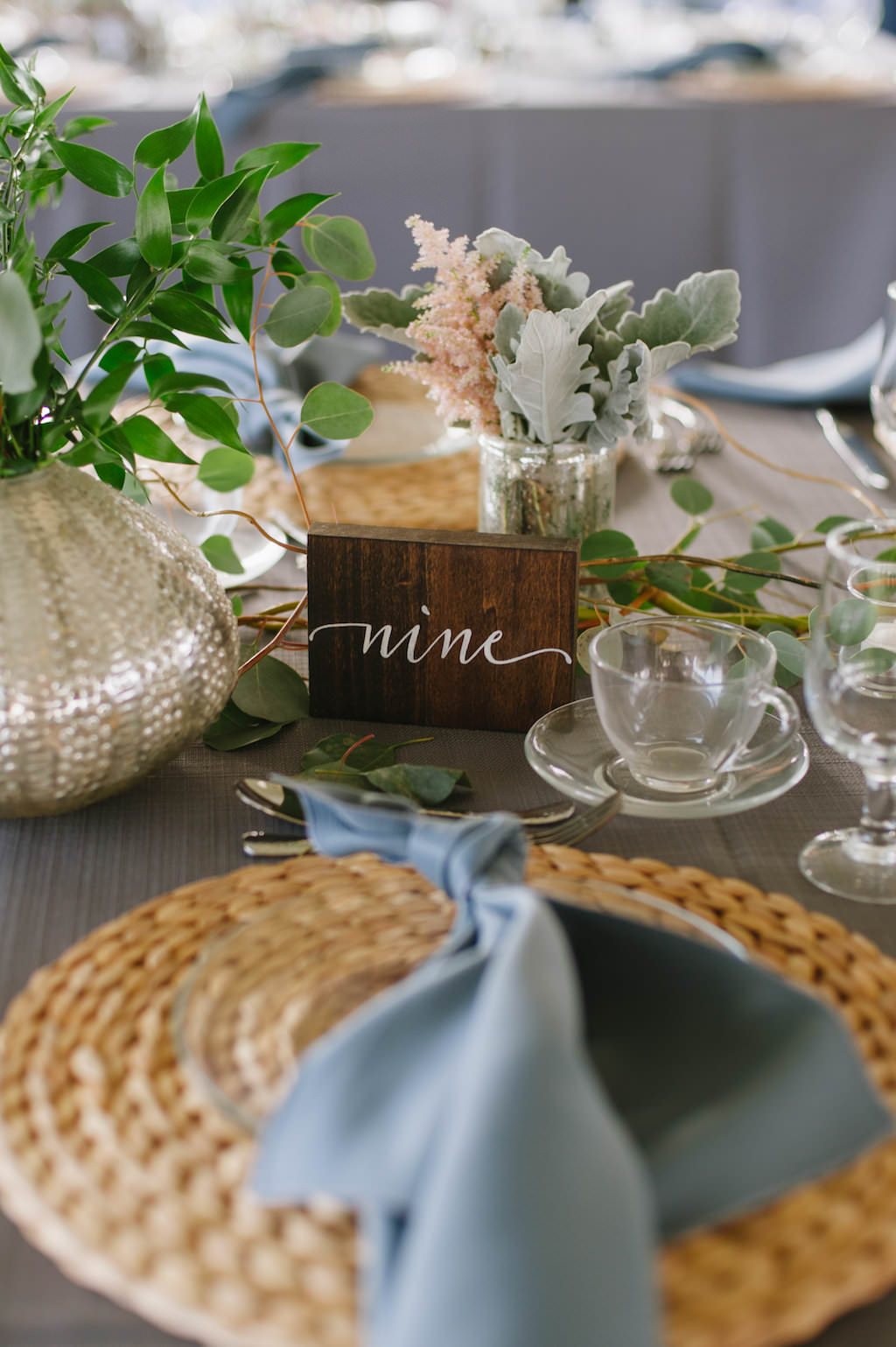 Outdoor Tented Wedding Reception with Organic Greenery Inspired Decor, Long Feasting Tables, Wicker Placemat Chargers, Wooden Table Numbers and Candle Centerpieces | Sarasota Wedding Planner Jennifer Matteo Event Planning