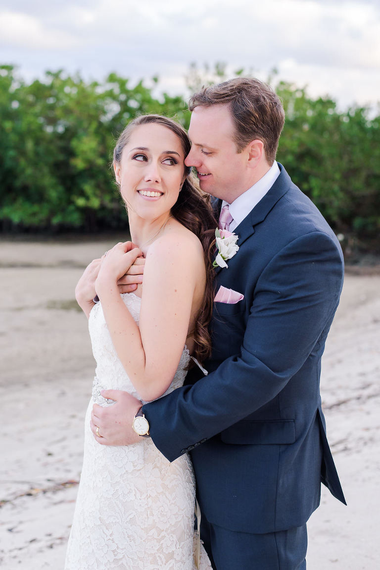 Beach Wedding Portrait, Bride in Lace Stella York Dress, Groom in Navy Blue Suit with Pink Tie and White Rose Boutonniere | Waterfront Hotel Wedding Venue The Westin Tampa Bay