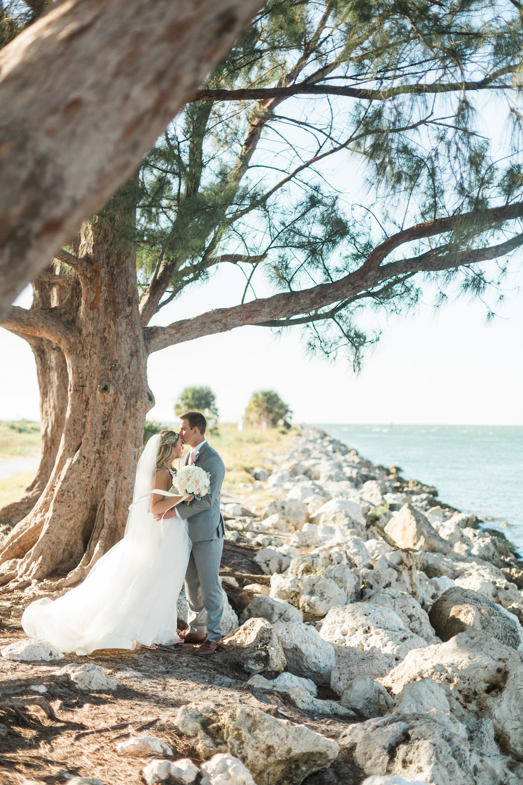 Outdoor Beach Wedding Bride and Groom Portrait, Groom in Gray Suit with Blush Pink Tie and Rose Boutonniere, Bride in Halter Ballgown Hayley Paige Wedding Dress with White Rose Bouquet and Jeweled Headband   Whimsical Clearwater Beach Wedding