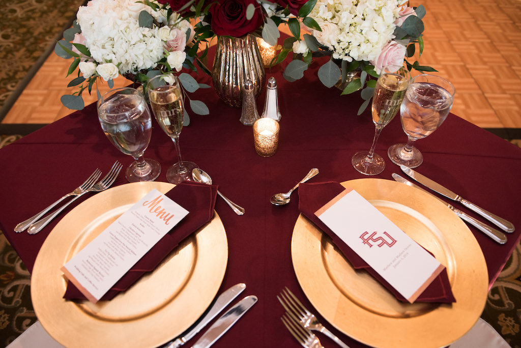 Gold and Burgundy FSU Alumni Wedding Reception Table Decor with small Red Rose, White Hydrangea, Blush Pink Floral and Greenery Centerpieces and Gold Printed Menu