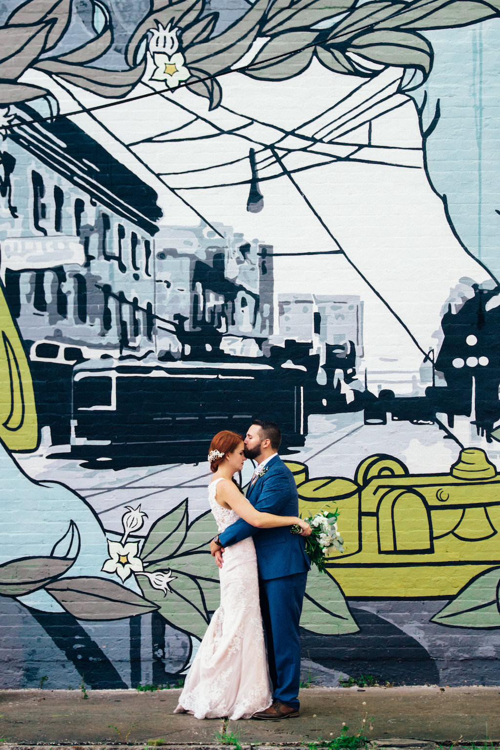 Downtown Tampa Creative Wedding Portrait, Bride in Sweetheart Lace Stella York Dress with White and Greenery Bouquet, Groom in Blue Suit