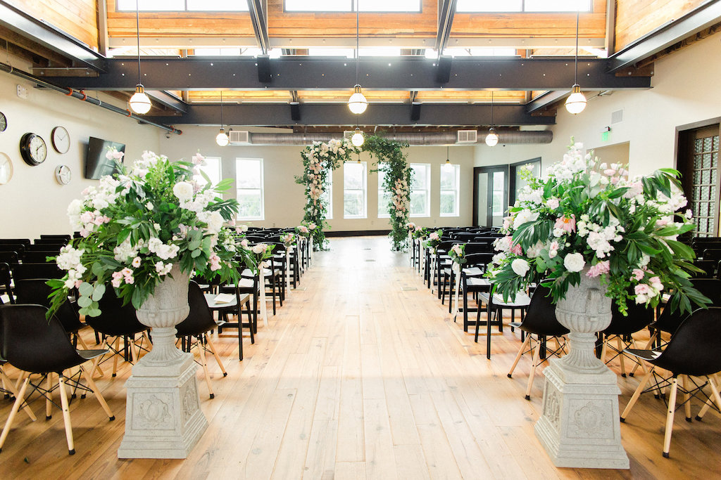 Indoor Industrial Garden Wedding Ceremony Decor with Floral and Greenery Arch, White and Blush Flower with Natural Greenery in Tall Planter, and Mismatched Dark Wooden Chairs   Tampa Bay Venue The Oxford Exchange
