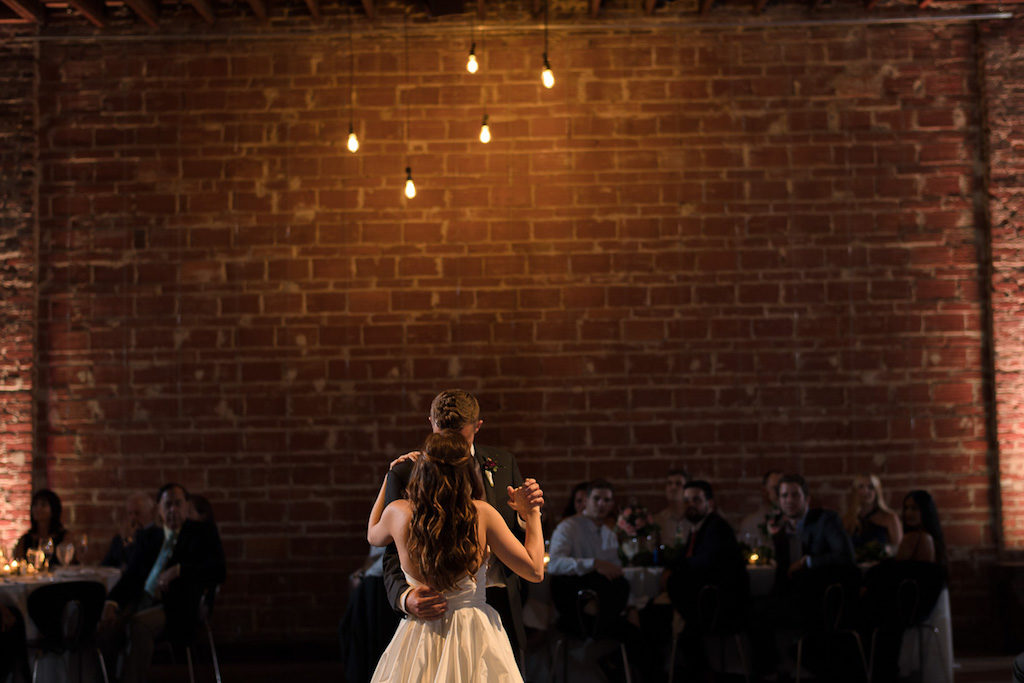Wedding Reception First Dance Portrait with Exposed Brick Wall and Hanging Edison Bulb Lights | Unique Downtown St Pete Wedding Venue NOVA 535